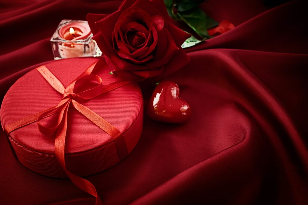Heart, flower, gift box, and candle on silk material