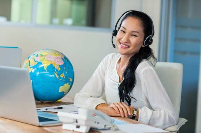 Travel with a headset in front of her compute with a globe