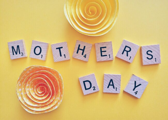 Mother's Day spelled out with scrabble letters in the middle of two paper flowers