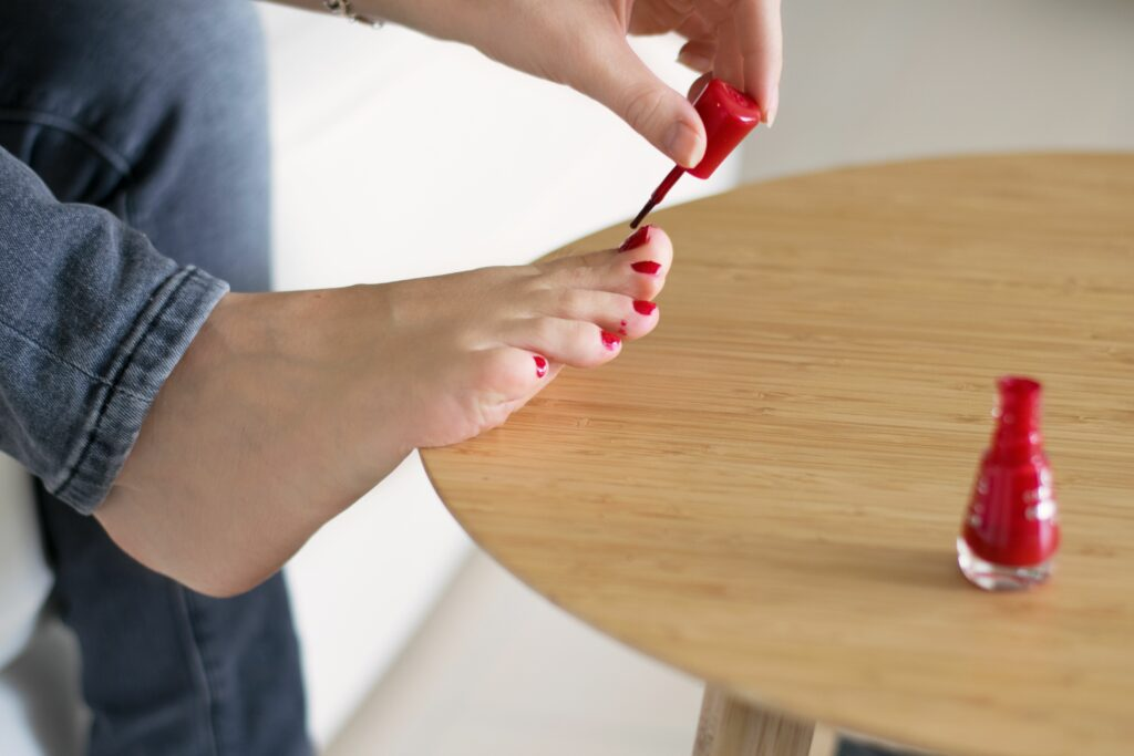 Woman painting toe nails with red polish