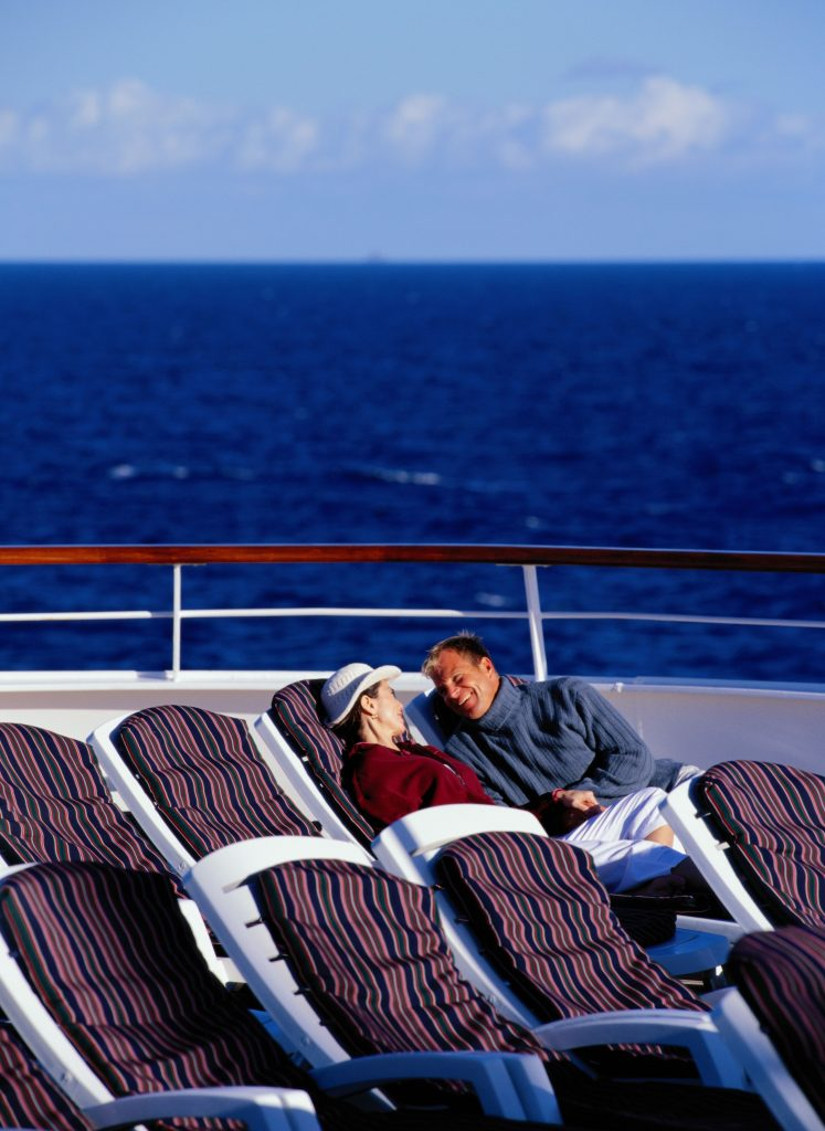 Couple lounging on lounge chairs on a cruise ship